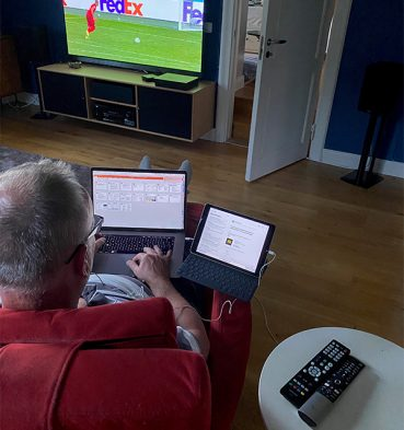 Man in front of three screens.