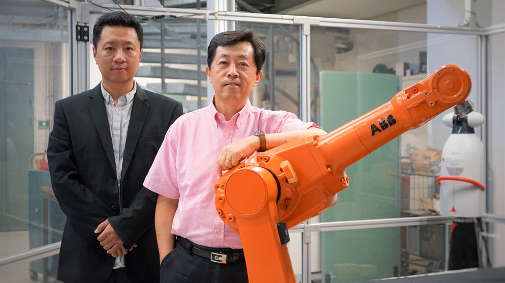 Vincent Wang and Lihui next to a ABB robot.