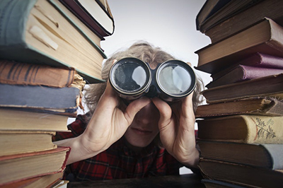 Man with binoculars between two stacks of books