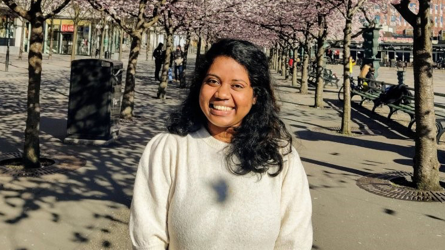 Aashlesha Chekkala posing in an arcade of cherry trees in Stockholm.
