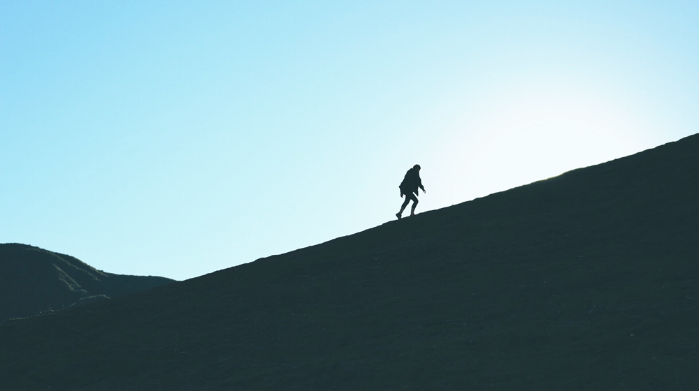 Man walking up a hill in counter light.