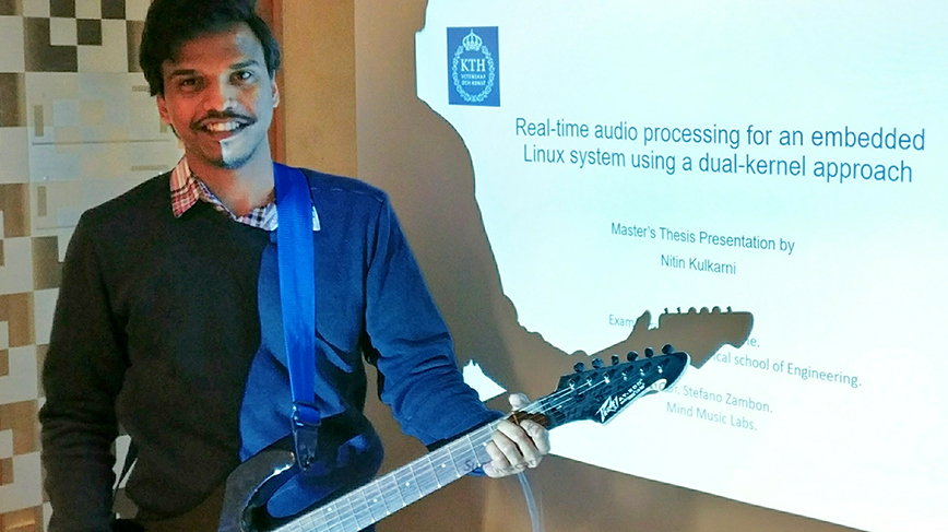 Nitin playing the  guitar during his master's presentation.