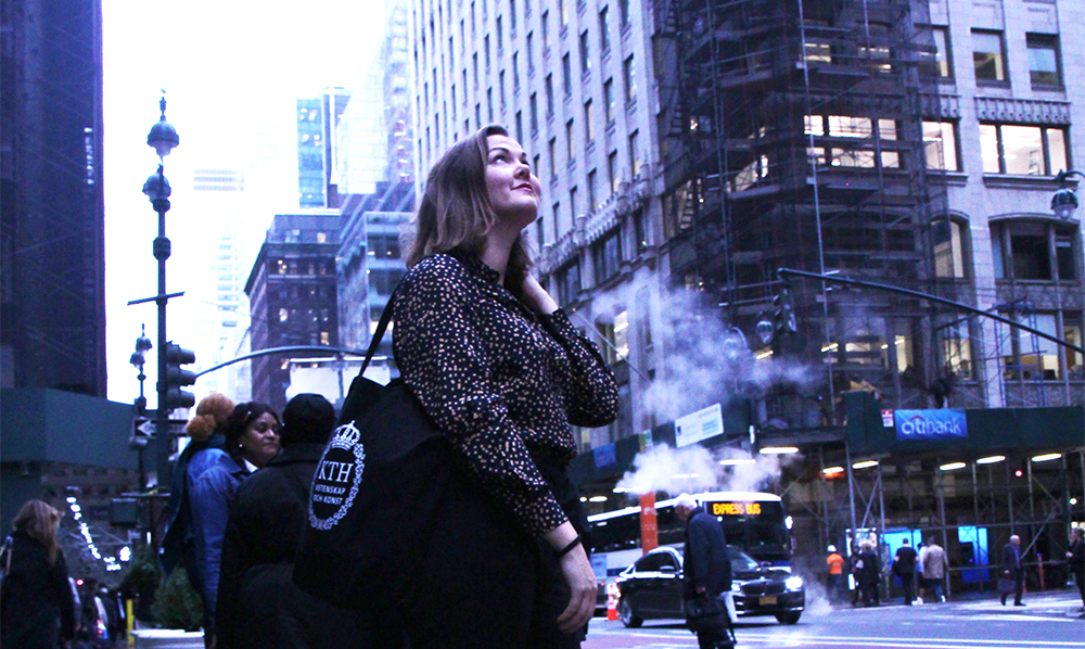 Lisa Bäckman looking up at the houses on a New York street with a KTH tote bag on her arm.