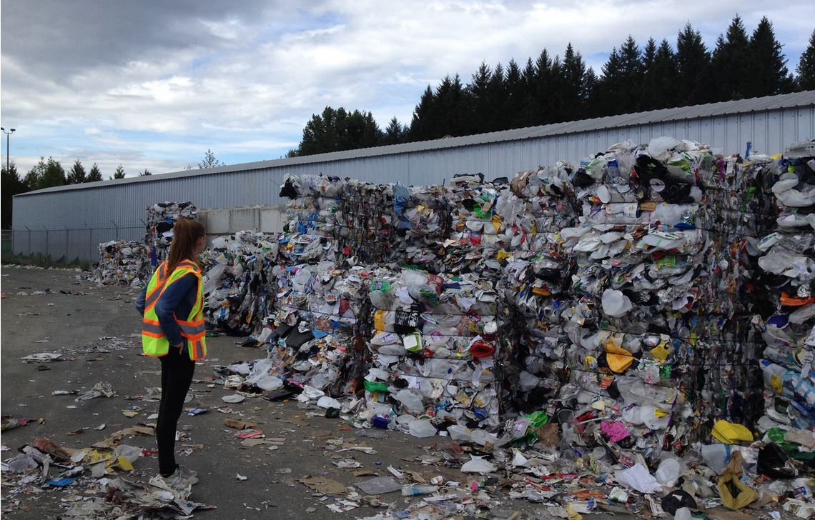 woman standing in front of garbage