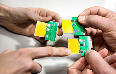 Four hands hold three silicon sensors.