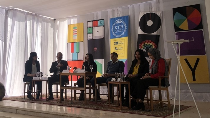 Six people sit on a low stage and participate in a panel discussion.