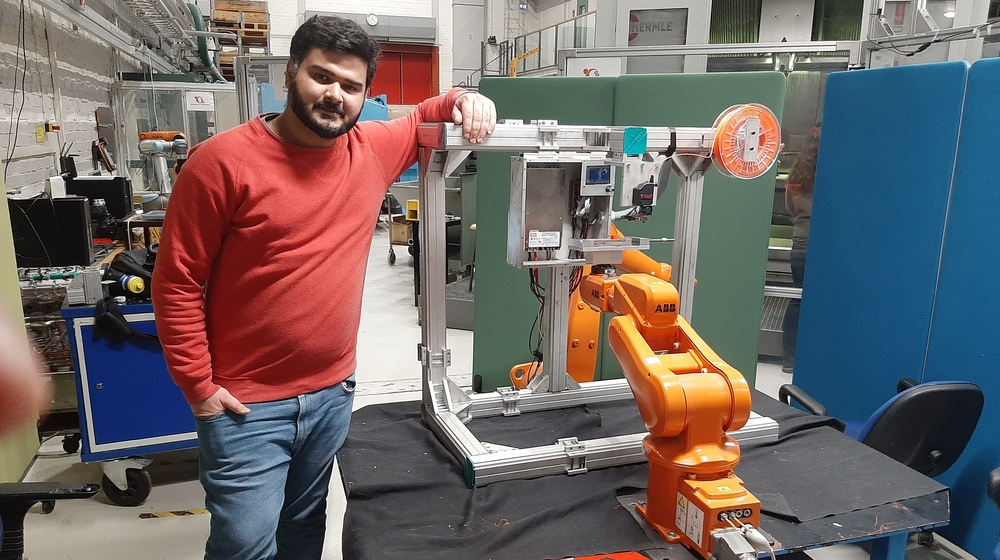 Fahad Ahmad Khan in front of the robot arm.