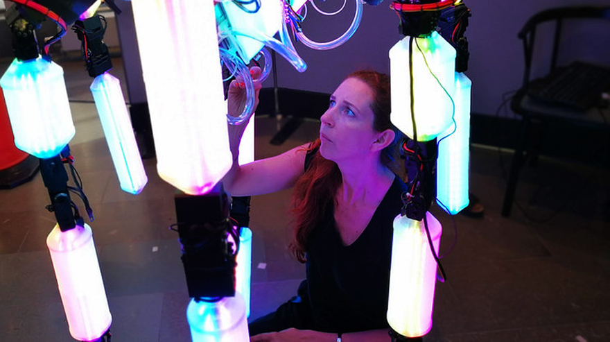A woman interacting with the robot sculpture.