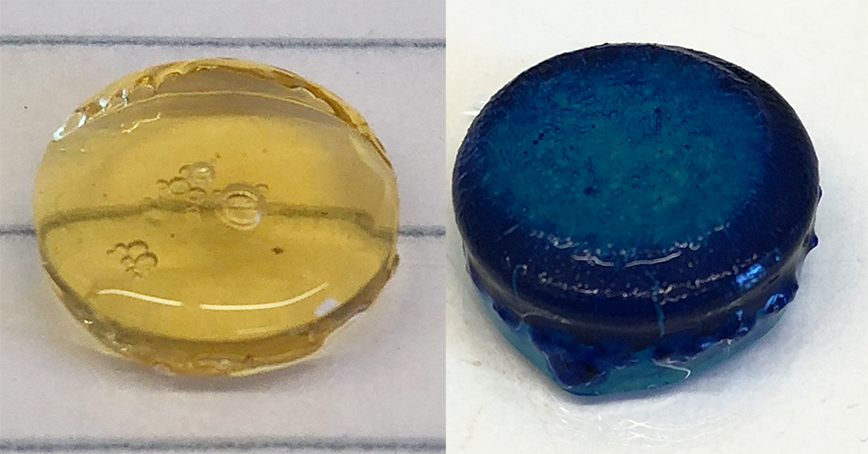 Two pellets, one translucent and golden, the other opaque and dark blue.