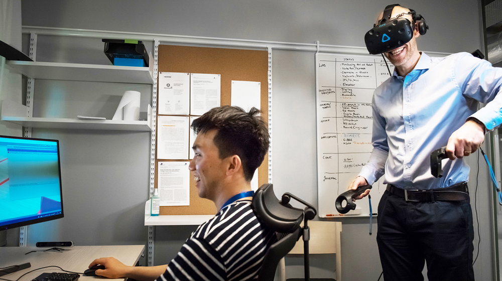 Magnus wearing VR glasses and tools in his hands while another man is sitting at a computer.
