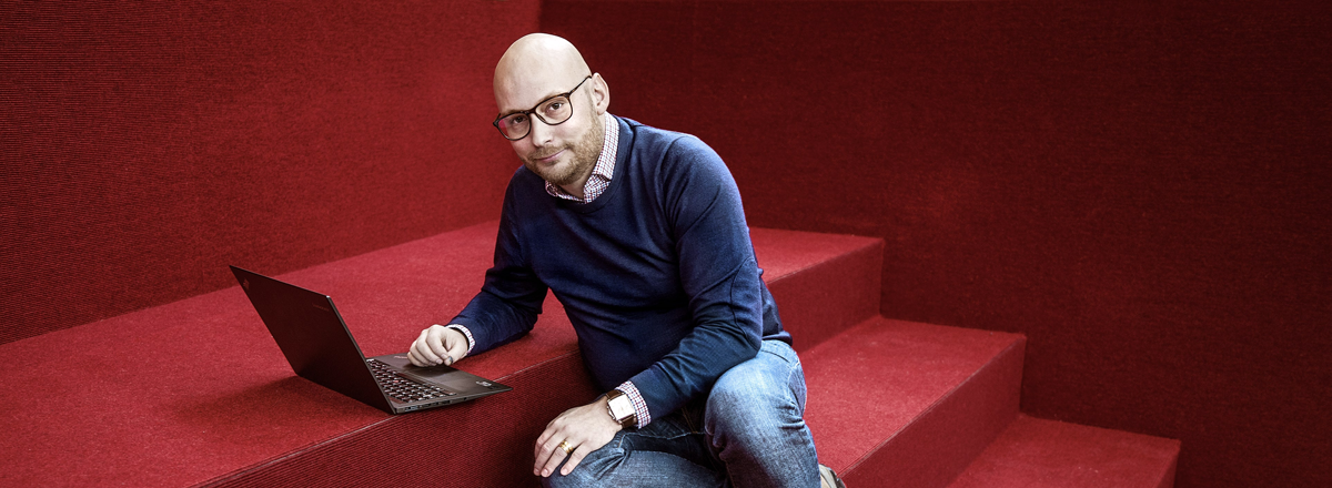 Visual interpretation: Stefan Stenbom sitting in red stairs with a laptop.
