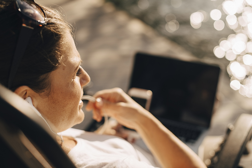 Woman sitting outdoors with a laptop in her lap.