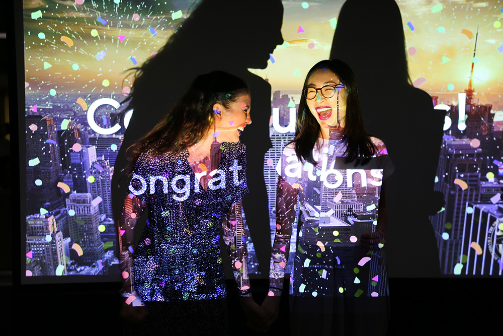 Jasmin Sabir and Selah Li celebrating their victory in front of a screen saying congratulations