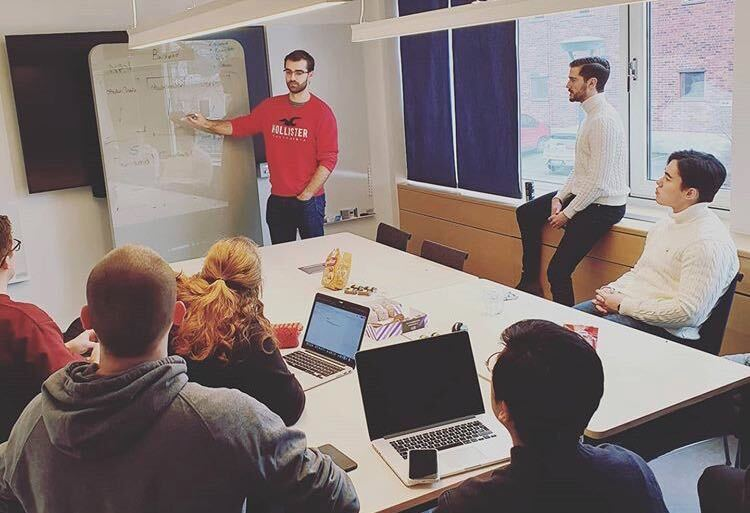 A meeting room. Mattias Bergström, a young man i a red shirt is holding a presentation pointing at a whiteboard. Five people are sitting around a table listening. One guy is leanign against the window sill.