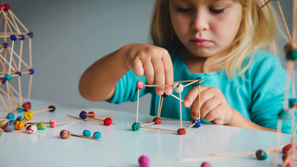 Young girl constructing things with clay and tooth sticks.