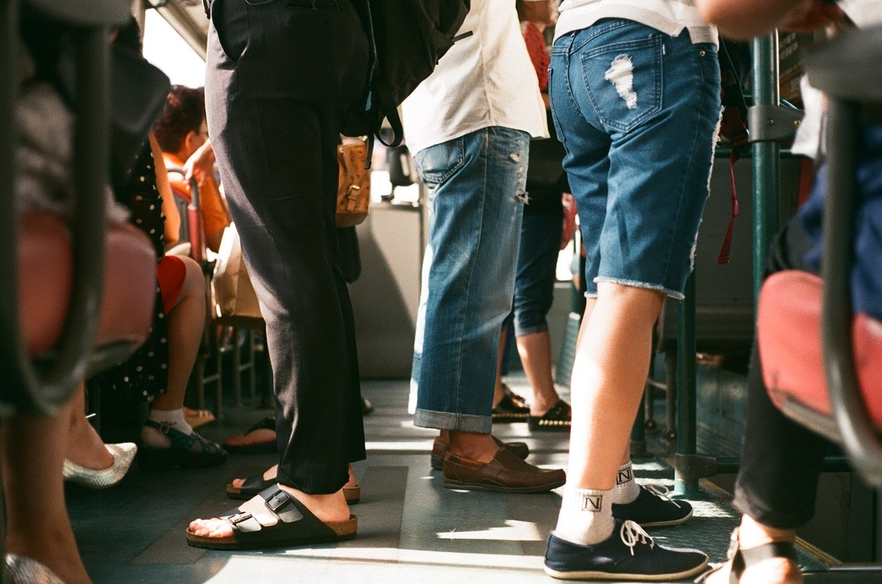 A full train cart, where you see the legs and feet of the passengers. Three people are in focus; one with black pants and birkenstock, one with jean shorts and sneakers and one with jeans and loafers. The sun shines in from the left.