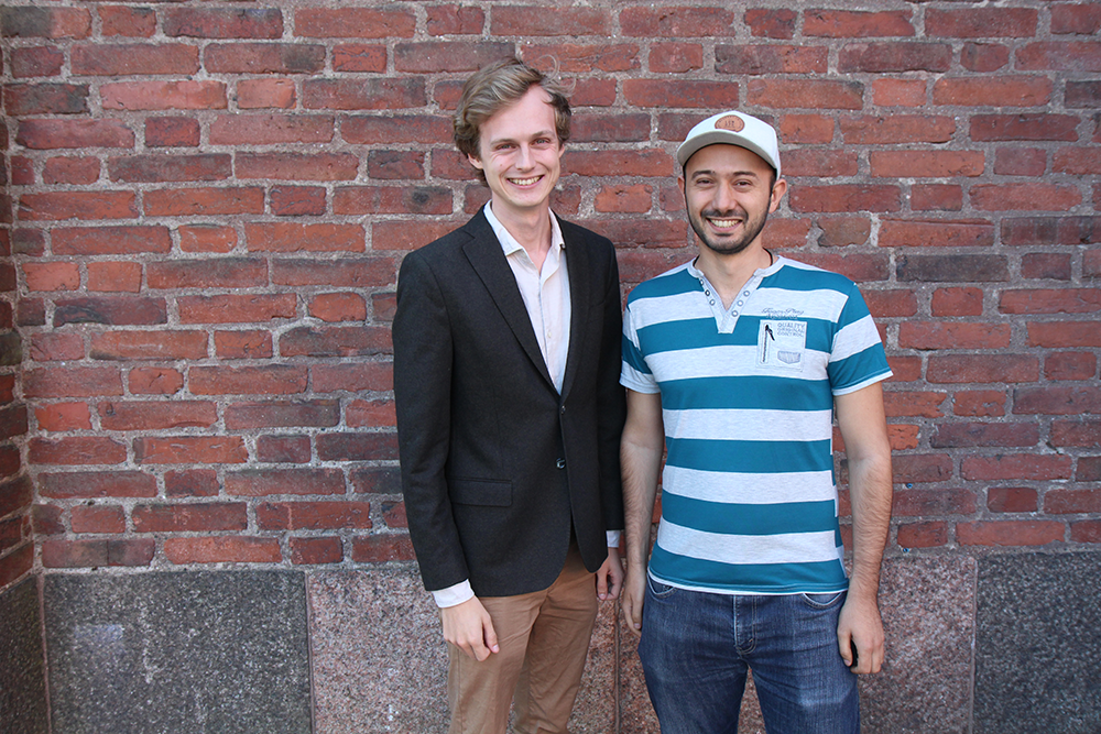 Oscar Örnberg to the left and Vahan Petrosyan to the right, standing in front of a red brick wall. Both are smiling. Oscar wears a black jacket and beige pants. Vahan has a cap, a blue and white striped t-shirt and jeans.